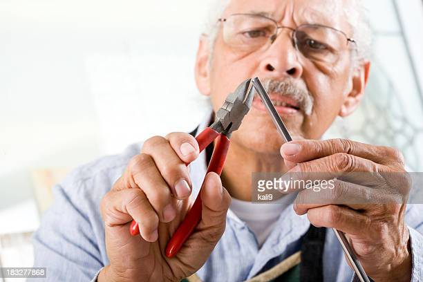Craftsman working with pliers and metal tube