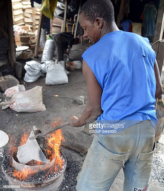 A craftsman works on a cooking pot in a forge in the neighbourhood of Adjame in Abidjan on August 14 2015 AFP PHOTO / ISSOUF SANOGO