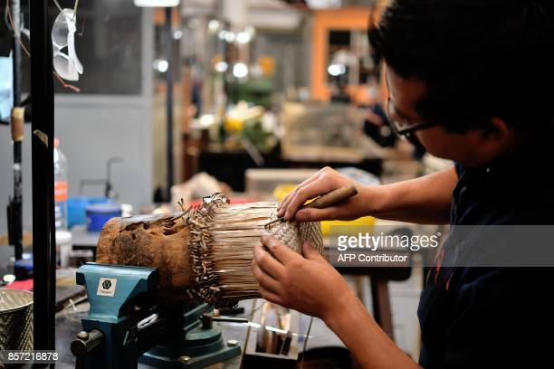 A craftsman works on a piece of silver in the workshop of the manufacturer of the formula one throphies during a tour by the manufacturer's house in...