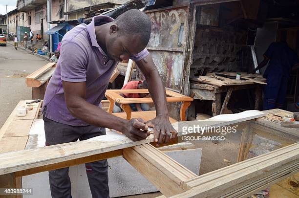 A craftsman works on a piece of wood in the neighbourhood of Adjame in Abidjan on August 14 2015 AFP PHOTO / ISSOUF SANOGO