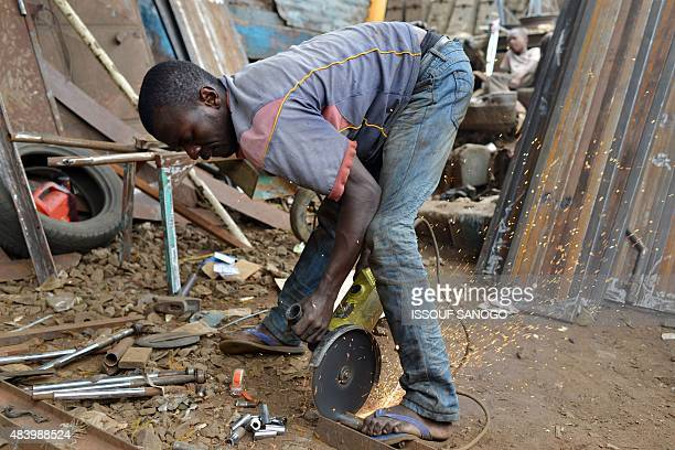 A craftsman works on metal in the neighbourhood of Adjame in Abidjan on August 14 2015 AFP PHOTO / ISSOUF SANOGO