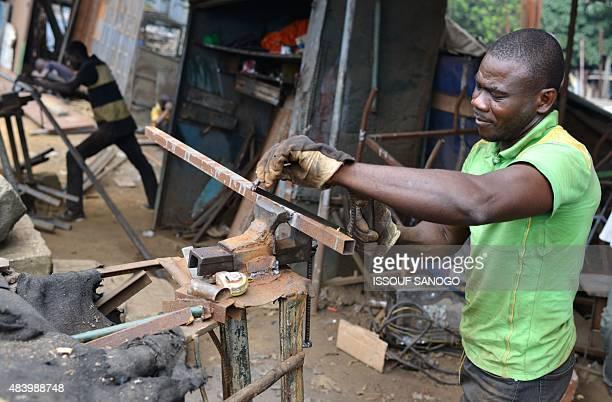 A craftsman works on metal in the neighbourhood of Adjame in Abidjan on August 14 2015 AFP PHOTO / ISSOUF SANOGO