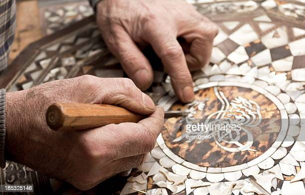 Craftsman's hands repairing a mosaic with sharp tool