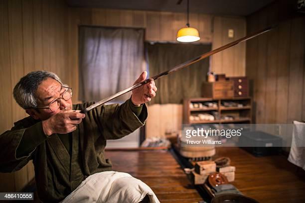 A craftsmen checks a traditional Japanese sword