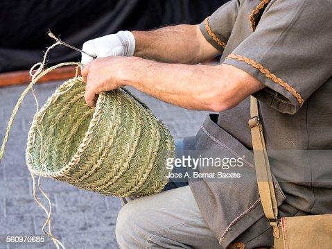 Craftsmen making up a basket of straw