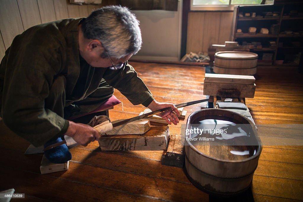 A craftsmen sharpens a traditional Japanese sword