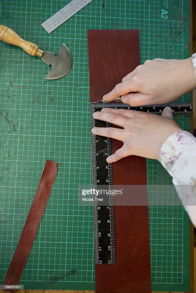 Craftsperson measuring and cutting leather. : Stock Photo