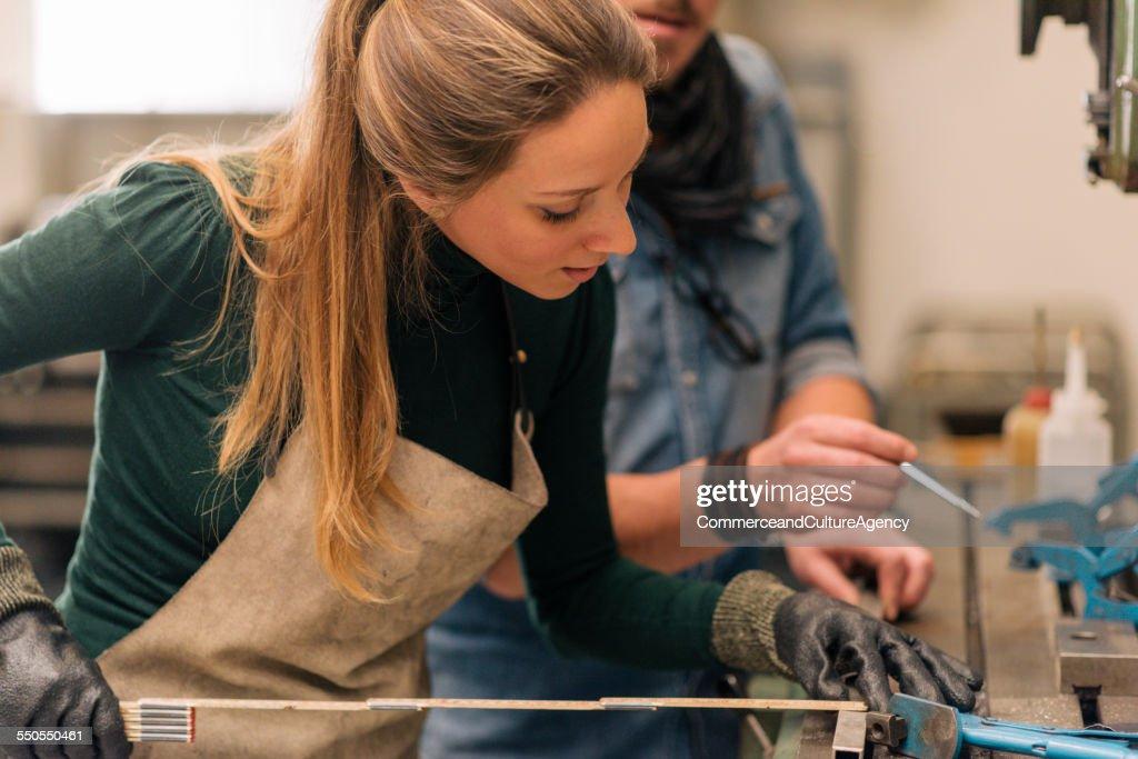 craftswoman and man in metal workshop measuring