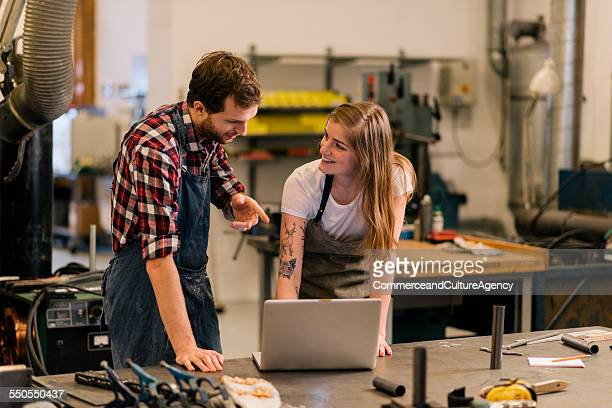 craftswoman and man working on laptop