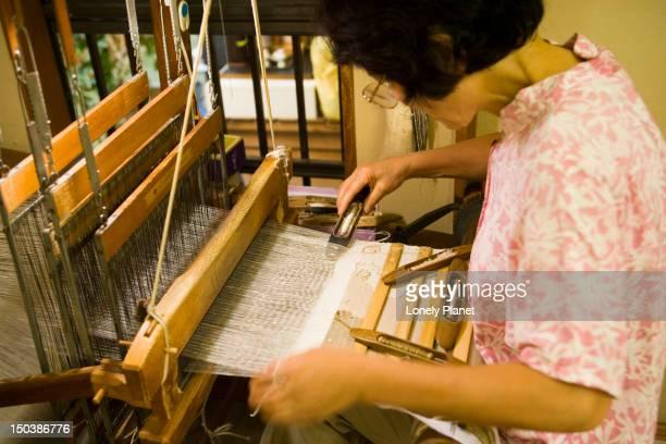 Craftswoman hand-weaving textiles on a hand loom, Nishiji Textiles.