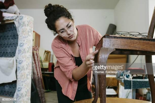 Artisane inspectant vieille chaise dans l'atelier de tapisserie d'ameublement