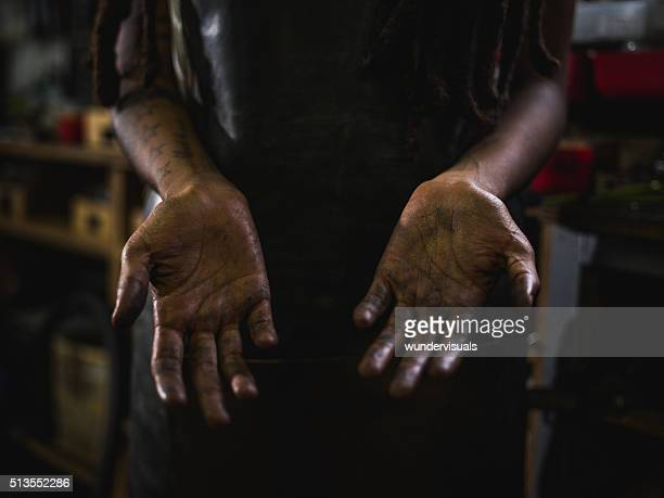 Craftswoman showing hands with grease and oil in the creases