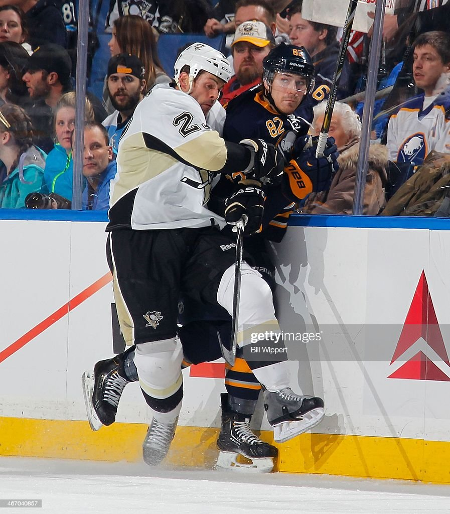 Craig Adams #27 of the Pittsburgh Penguins checks Marcus Foligno #82 of the Buffalo Sabres on February 5, 2014 at the First Niagara Center in Buffalo, New York.