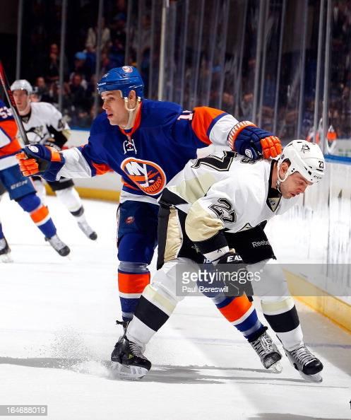 Craig Adams of the Pittsburgh Penguins is held off by Marty Reasoner of the New York Islanders in an NHL hockey game at Nassau Veterans Memorial...