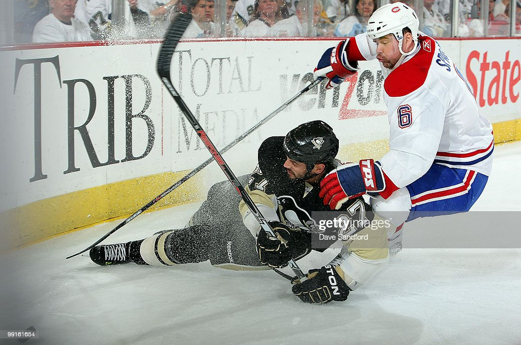 <a gi-track='captionPersonalityLinkClicked' href=/galleries/search?phrase=Craig+Adams&family=editorial&specificpeople=211144 ng-click='$event.stopPropagation()'>Craig Adams</a> #27 of the Pittsburgh Penguins is taken out by <a gi-track='captionPersonalityLinkClicked' href=/galleries/search?phrase=Jaroslav+Spacek&family=editorial&specificpeople=204681 ng-click='$event.stopPropagation()'>Jaroslav Spacek</a> #6 of the Montreal Canadiens in Game Seven of the Eastern Conference Semifinals during the 2010 Stanley Cup Playoffs at Mellon Arena on May 12, 2010 in Pittsburgh, Pennsylvania. The Canadiens defeated the Penguins 5-2 to win the series 4-3 and advance to the Conference Finals.