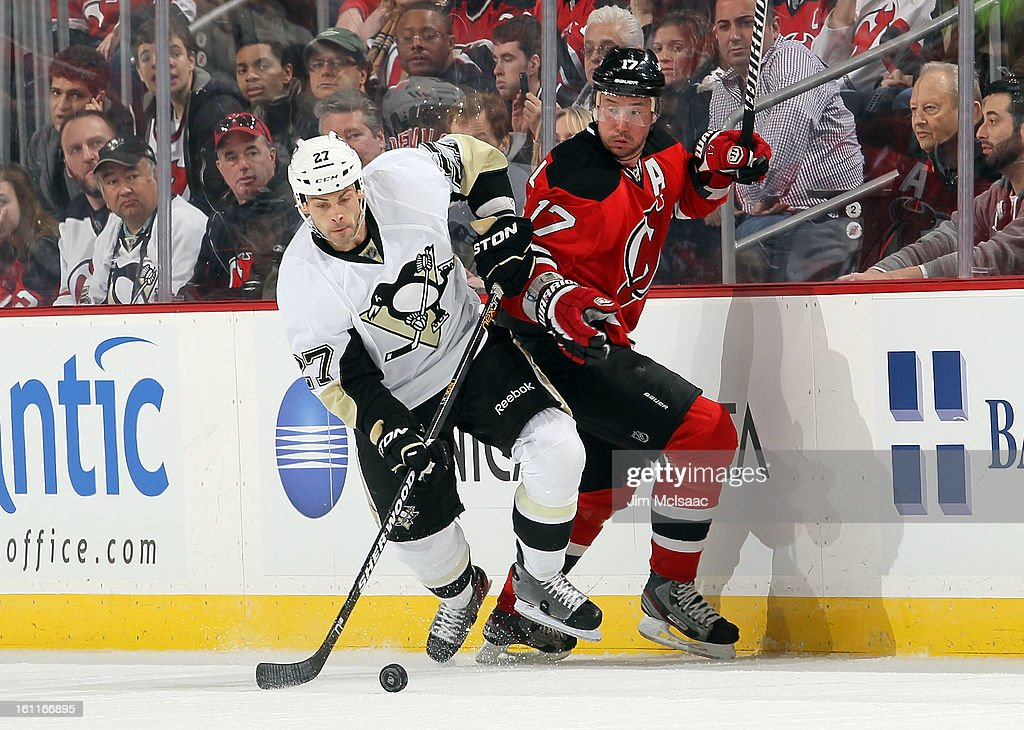 Craig Adams #27 of the Pittsburgh Penguins plays the puck in the first period against Ilya Kovalchuk #17 of the New Jersey Devils at the Prudential Center on February 9, 2013 in Newark, New Jersey.
