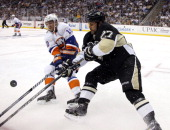 Craig Adams of the Pittsburgh Penguins skates against Keith Aucoin of the New York Islanders in Game Five of the Eastern Conference Quarterfinals...