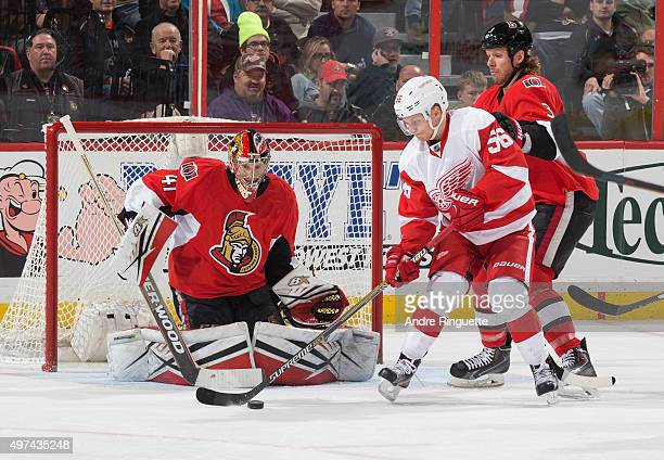 Craig Anderson and Marc Methot of the Ottawa Senators defend their net as Teemu Pulkkinen of the Detroit Red Wings deflects a shot on goal at...