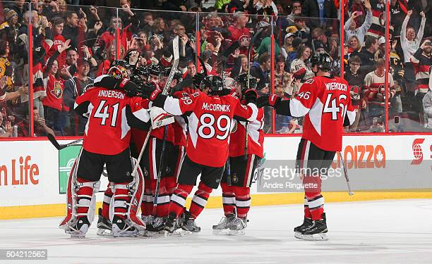 Craig Anderson Max McCormick and Patrick Wiercioch of the Ottawa Senators celebrate their overtime win against the Boston Bruins with teammates at...