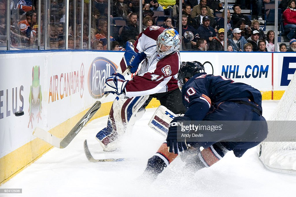 Craig Anderson of the Colorado Avalanche plays the puck past a defending Shawn Horcoff of the Edmonton Oilers at Rexall Place on October 27 2009 in...
