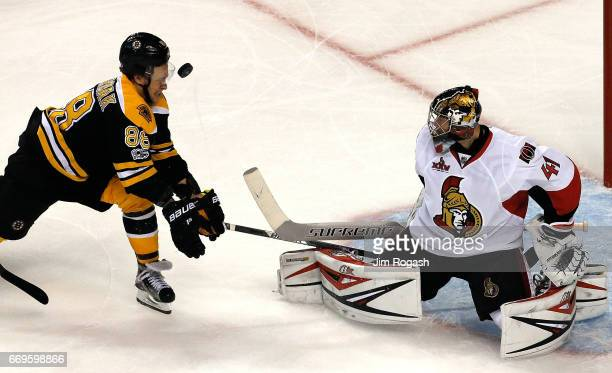 Craig Anderson of the Ottawa Senators defends the net as David Pastrnak of the Boston Bruins is hit in the face by the puck in the third period in...