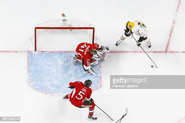 Craig Anderson of the Ottawa Senators guards his net as Cody Ceci defends against Sidney Crosby of the Pittsburgh Penguins in Game Four of the...