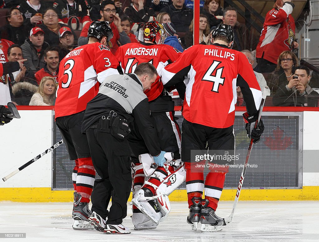 <a gi-track='captionPersonalityLinkClicked' href=/galleries/search?phrase=Craig+Anderson&family=editorial&specificpeople=211238 ng-click='$event.stopPropagation()'>Craig Anderson</a> #41 of the Ottawa Senators is helped off the ice by team mates <a gi-track='captionPersonalityLinkClicked' href=/galleries/search?phrase=Marc+Methot&family=editorial&specificpeople=2216900 ng-click='$event.stopPropagation()'>Marc Methot</a> #3 and Chris Phillips #4 and Head Athletic Therapist Gerry Townend after being injured in a play, during an NHL game against the New York Rangers, at Scotiabank Place on February 21, 2013 in Ottawa, Ontario, Canada.