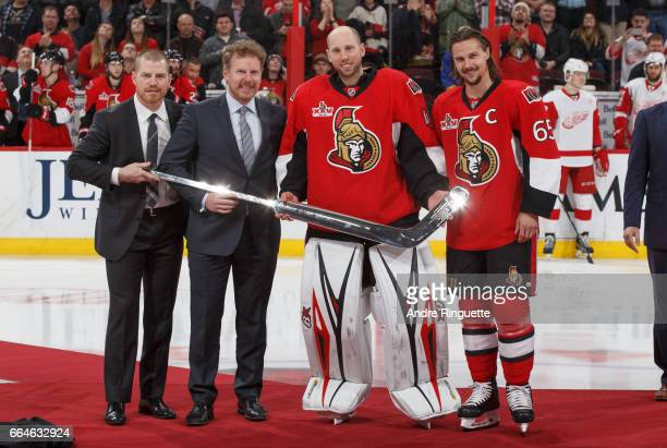 Craig Anderson of the Ottawa Senators is presented with a silver stick by Chris Neil Daniel Alfredsson and Erik Karlsson as he is honored for having...