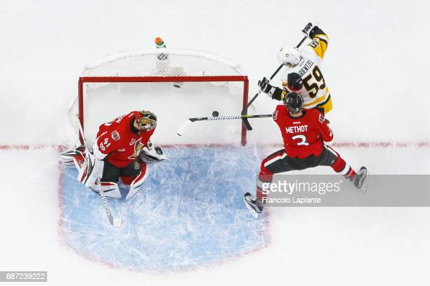 Craig Anderson of the Ottawa Senators looks behind as the puck passes the goal line as Marc Methot defends against Jake Guentzel of the Pittsburgh...