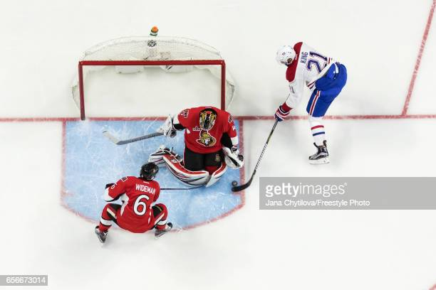 Craig Anderson of the Ottawa Senators makes a pad save against Dwight King of the Montreal Canadiens as Chris Wideman of the Ottawa Senators defends...