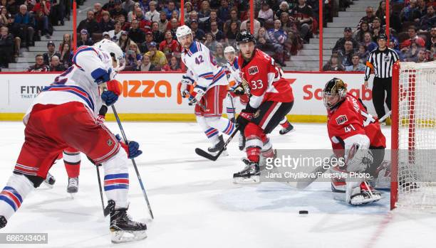 Craig Anderson of the Ottawa Senators makes a pad save against Matt Puempel of the New York Rangers as Fredrik Claesson of the Ottawa Senators and...