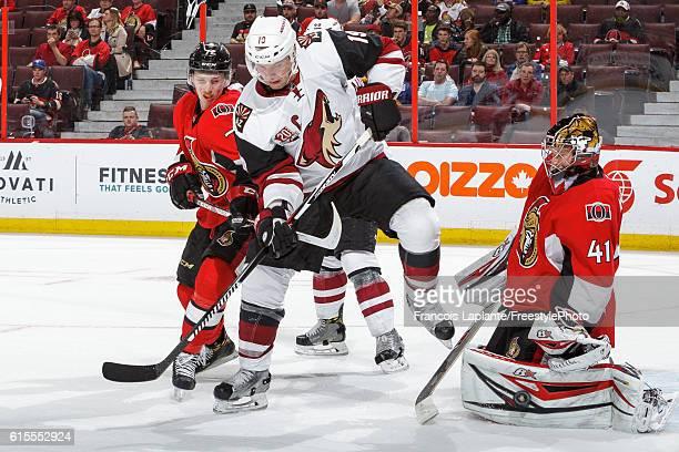 Craig Anderson of the Ottawa Senators makes a pad save as Thomas Chabot defends against Shane Doan of the Arizona Coyotes during an NHL game at...