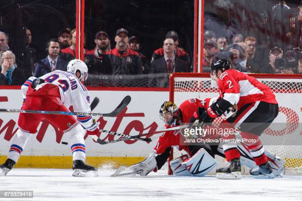 Craig Anderson of the Ottawa Senators makes a paddle save against Mika Zibanejad of the New York Rangers as Dion Phaneuf of the Ottawa Senators in...