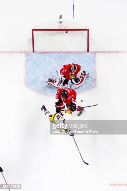 Craig Anderson of the Ottawa Senators makes a save against Bryan Rust of the Pittsburgh Penguins as Dion Phaneuf of the Senators defends the net in...