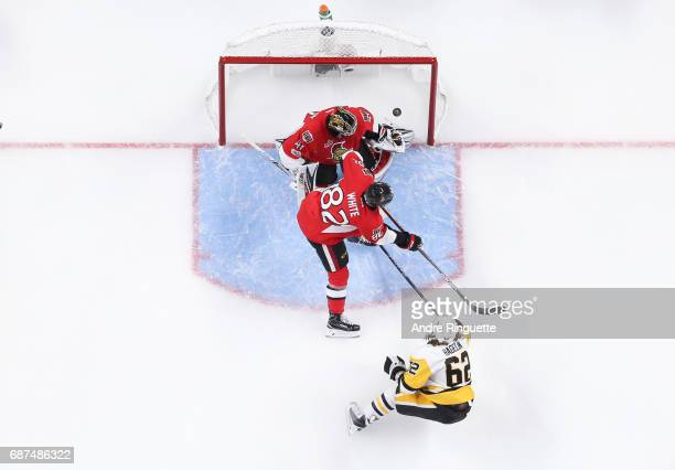 Craig Anderson of the Ottawa Senators makes a save against Carl Hagelin of the Pittsburgh Penguins as teammate Colin White supports on the play in...