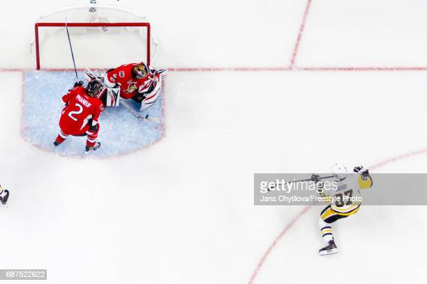 Craig Anderson of the Ottawa Senators makes a save against Sidney Crosby of the Pittsburgh Penguins as Dion Phaneuf of the Senators looks on in the...