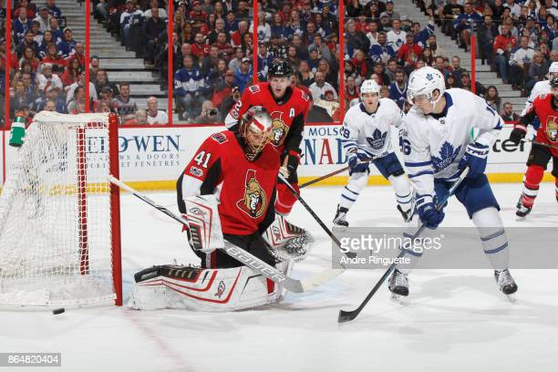 Craig Anderson of the Ottawa Senators makes a save as Mitchell Marner of the Toronto Maple Leafs screens on the play at Canadian Tire Centre on...
