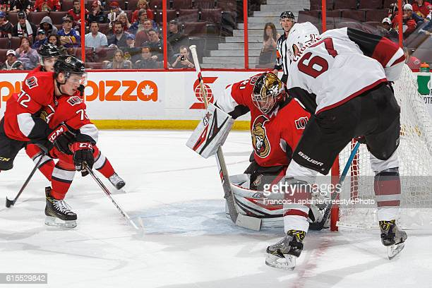 Craig Anderson of the Ottawa Senators makes a save as teammate Thomas Chabot defends against Lawson Crouse of the Arizona Coyotes during an NHL game...