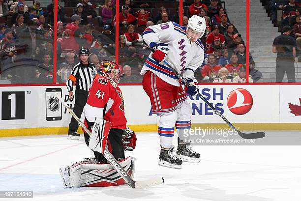 Craig Anderson of the Ottawa Senators makes a save despite a screen by a jumping Chris Kreider of the New York Rangers during an NHL game at Canadian...