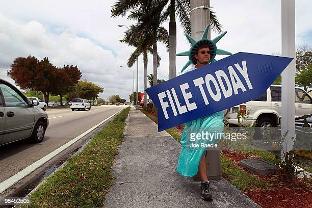 Craig Baldwin holds a sign advertising a tax preparation office for people that still need help completing their taxes before the Internal Revenue...