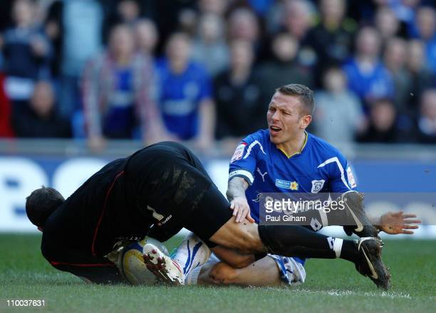Craig Bellamy of Cardiff City battles for the ball with Luke Steele of Barnsley during the npower Championship match between Cardiff City and...