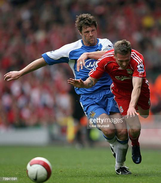 Craig Bellamy of Liverpool is tackled by Arjan De Zeeuw during the Barclays Premiership match between Liverpool and Wigan Athletic at Anfield on...
