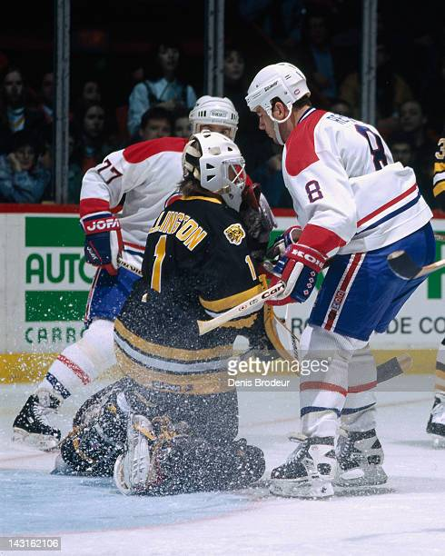 Craig Billington of the Boston Bruins makes a save while Mark Recchi and Pierre Turgeon of the Montreal Canadiens stand over him Circa 1995 at the...