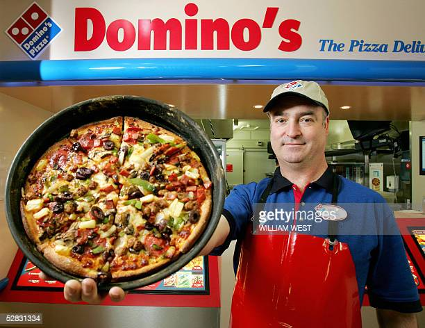 Craig Birchall a Domino's Pizza franchisee displays his super supreme pizza in the pizzasaturated suburb of Carlton in Melbourne 16 May 2005 as...