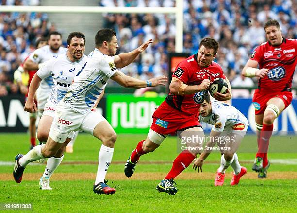 Craig Burden of the Rugby Club Toulonnais runs with the ball against Remy Grosso of Castres Olympique during the Top 14 Final game at Stade de France...