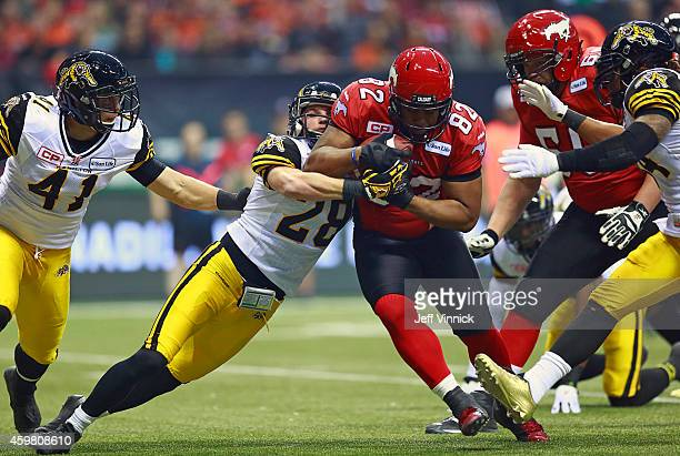 Craig Butler of the Hamilton TigerCats tackles Nik Lewis of the Calgary Stampeders during the 102nd Grey Cup Championship Game at BC Place November...