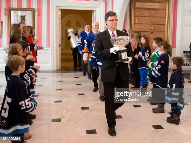 Craig Campbell of the Hockey Hall of Fame carries in the original bowl of the Stanley Cup during the Stanley Cup Homecoming as part of the Stanley...