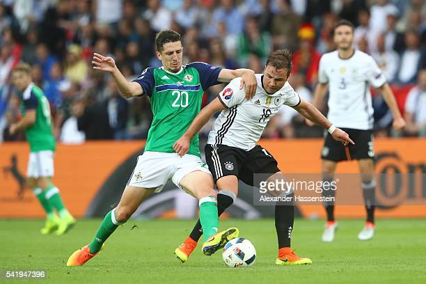 Craig Cathcart of Northern Ireland and Mario Goetze of Germany compete for the ball during the UEFA EURO 2016 Group C match between Northern Ireland...