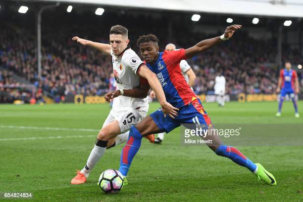 Craig Cathcart of Watford and Wilfried Zaha of Crystal Palace battle for possession during the Premier League match between Crystal Palace and...