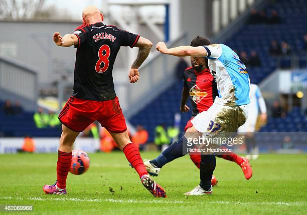 Craig Conway of Blackburn Rovers shoots past Jonjo Shelvey of Swansea City to score their third goal during the FA Cup Fourth Round match between...